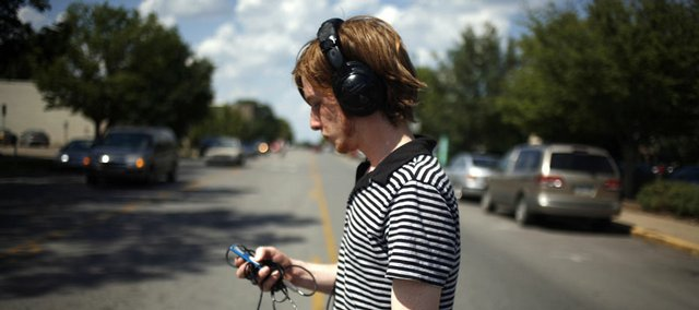 Chris Clark, a Kansas University student from St. Louis, flips through his MP3 player Friday while walking through downtown Lawrence. Clark, who masters music, says he tries to keep music at a reasonable level because his hearing is key to what he does.