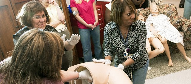 Starr Williams, center, a registered nurse at Kansas University Hospital, reacts as she approaches a pelvic mannequin during a breech birth training situation Tuesday at the hospital in Kansas City, Kan. KU Hospital will be training doctors around the country in such obstetrical emergency situations using the mannequins.