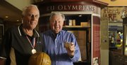 Former Olympic champions Bill Lienhard, left, and Charlie Hoag, show their gold medals in front of the KU Olympian display at the Booth Family Hall of Athletics on Monday at Allen Fieldhouse.