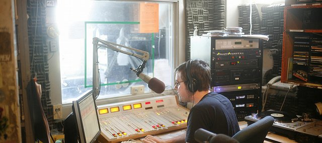 "Kansas University senior Ian Hrabe runs his radio show this summer at the KJHK ""shack"" northwest of Memorial Stadium. ""It's sad to lose the shack because it's what KJ is,"" Hrabe said, ""but we're basically being kicked out because it's falling apart."""