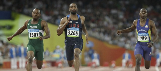 Tyson Gay of the United States, center, leads Nigeria's Olusoji Fasuba, left, and Colombia's Daniel Grueso across the finish line during a 100 meter preliminary heat on Friday in Beijing.
