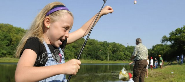 Eight-year-old Elisa Jalenak, Lawrence, gets excited as her recently caught fish begins to flop around on the hook during a day of free fishing for kids Saturday, Aug. 16, 2008 around Lake Henry at Clinton Lake State Park. Prizes were awarded for both the largest and smallest fish.