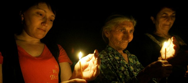 Ossetian women light candles early today in memory of victims in South Ossetia during an observance in Vladikavkaz, the provincial capital of the region of North Ossetia, Russia.