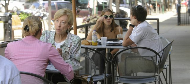 Lindsay Buscher, left, of Lawrence, and Karen Rippel, of Topeka, enjoy an outdoor lunch Monday on Massachusetts Street. The city is considering lifting a long-standing ban against downtown bars applying for sidewalk seating areas.