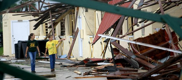 Two children walk among the damage to barns Tuesday in Wellington, Fla. Tropical Storm Fay rolled ashore Tuesday short of hurricane strength but mysteriously gained speed as it headed over land, bringing heavy rain, high wind and tornadoes.