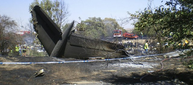 Public safety workers and vehicles are seen near the tail of the Spanair jet that crashed during takeoff Wednesday at Madrid's Barajas International Airport. The airliner, bound for the Canary Islands at the height of the vacation season, crashed, burned and broke into pieces, killing at least 153 people on board, officials said. Only 19 people survived.