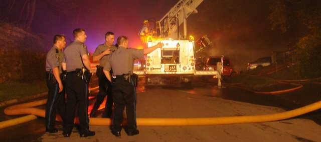 Lawrence Police officers watch the intersection of 9th and Indiana while Lawrence firefighters battle an early morning blaze at 1005 Indiana in this July 31, 2008 file photo. Lawrence police officers and firefighters would receive a raise less than the 1.5 percent raise received in 2009 under the tentative agreement that city commissioners will consider Tuesday.