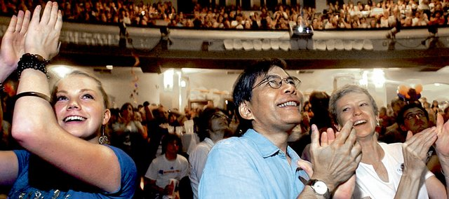 Supporters of Barack Obama, from left, Katrina Connor, Don Low and Diane Low, all of Lawrence, applaud as the Illinois senator is introduced Thursday during the Democratic National Convention in Denver. Hundreds of local Obama supporters gathered at a party at Liberty Hall to see him accept his party's presidential nomination.