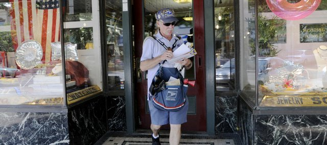 Jerry Totten completes a mail delivery at Mark's Jewelers, 817 Mass. Totten is Lawrence's only full-time, walking mail carrier, and his route includes most of downtown.
