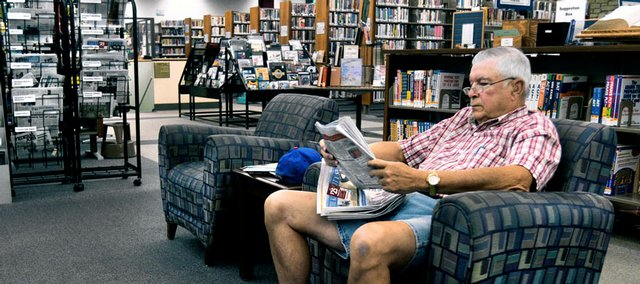 Lawrence resident Gary Moulton reads a newspaper last week at the Lawrence Public Library, 707 Vt. The library's director would like to rearrange the library and add more space for teenagers.