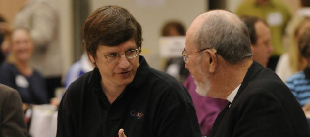 Brian McClendon, who grew up in Lawrence and oversees Geo products, including Google Earth, visits with longtime friend Bob Moore before speaking Thursday morning at The Community Education breakfast at the Lawrence Holidome.