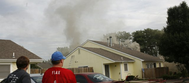 Neighbors watch as firefighters respond to a structure fire Friday at 2832 Iowa Street. No one was injured in the fire but six people were displaced. The fire started in an unoccupied unit, witnesses said.