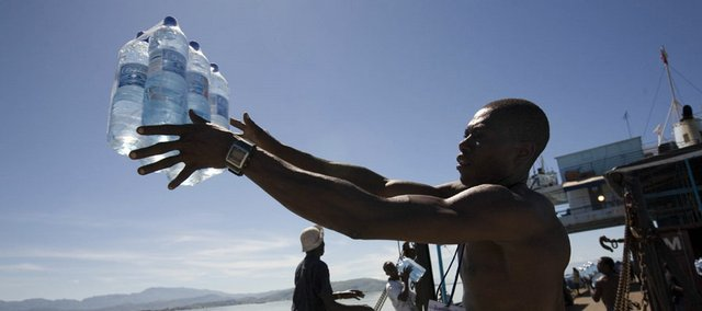 A man unloads water donated by World Food Program on Friday in Gonaives, Haiti. A ship carrying U.N. relief supplies managed to dock Friday, the first significant aid delivery after four days without food or water for Hanna survivors.
