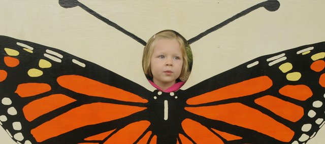Madison Kuhle, 5, Lawrence, poses as a butterfly for her father at the Monarch Watch open house Saturday at Foley Hall on Kansas University's campus.