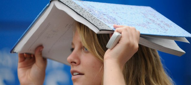 Hayley Mallen, a kansas University freshman from Kansas City, Kan., uses a textbook to stay dry on Friday.