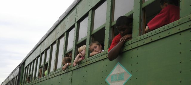 Children peek out the window of the Midland Railway train in Baldwin City before the train took off Saturday. About 200 passengers participated in the event to honor children living with cancer and victims.