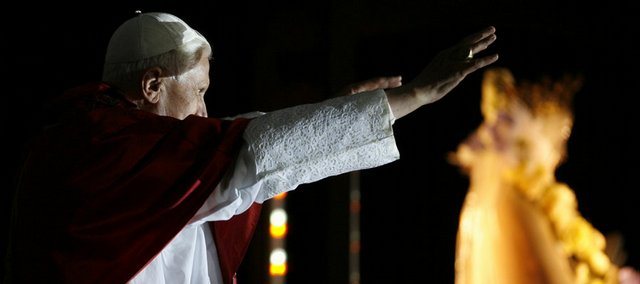 Pope Benedict XVI greets faithful at the end of a candle procession for the Virgin Mary on Saturday at the Lourdes shrine, southwestern France.The pontiff celebrated the 150th anniversary of apparitions of the Virgin Mary to local 14-year-old girl, Bernadette Soubirous. The shrine draws 6 million people annually, some of them disabled or desperately sick, many of them hoping for a miracle.
