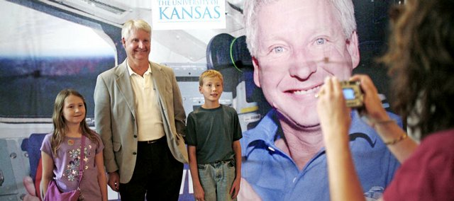 Jessica Roberts, 8, left, and Nathan Roberts, 10, pose for a picture with KU professor and former NASA astronaut Steve Hawley while attending a lecture series called CLAS ACTS at Spooner Hall. The series allows KU professors to give lectures to the public about their field. At right, Lisa Roberts took a picture of the group Sunday in front of a backdrop of Hawley during his astronaut days.