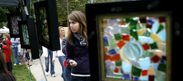 Jennifer Holladay, of Lawrence, checks out a selection of art Sunday during the Fall Arts and Crafts Festival at South Park. The framed glass was at the booth of Kickin' Glass, of Manhattan.