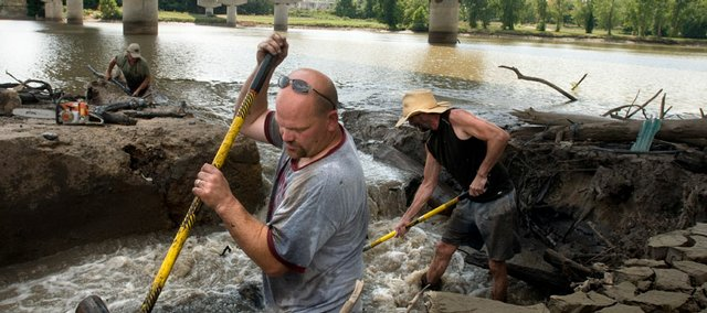 Bowersock Mills & Power Co. workers Mark Maxwell, front, Brian Farley, right, and Rich Foreman, back left, clear debris from the lift gates on the north bank of the Kansas River to better control the flow of the river Aug. 28.