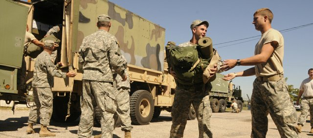 National Guardsmen Brad Henning, left, and Walter Clinton help unload supplies in Lawrence after returning Wednesday from a deployment to Baton Rouge where they helped with relief after Hurricane Gustav. About 28 local guardsmen deployed and helped with security and distributing aid.