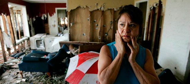 Korkie Smith looks Tuesday at the devastation of her neighbor Renee Napier's house in Baytown, Texas, in the aftermath of Hurricane Ike.