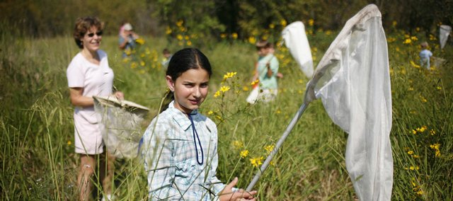 Annabell Davis, 9, center, stalks a monarch butterfly during a tagging event at the Baker Wetlands. The Jayhawk Audubon Society and Monarch Watch coordinated the event, in which participants caught and tagged butterflies for tracking purposes during their annual migration. About 500 people helped with the project on Saturday morning.