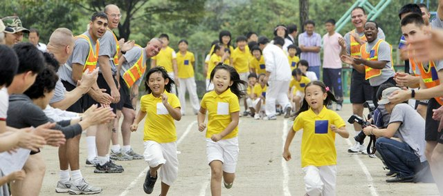 South Korea's Taesungdong Elementary School students participate Tuesday in an athletic meet as U.S. soldiers from the United Nations Command cheer them on. Taesungdong Elementary School is located in the only South Korean village inside the demilitarized zone between North and South Korea.