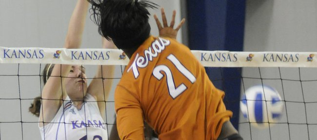 Kansas players Nicole Tate (13) and Brittany Williams (10) attempt to block a spike by Texas' Destinee Hooker on Saturday at the Horejsi Center.