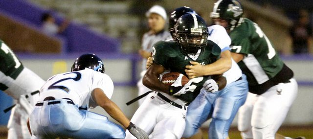 Free State High senior Chucky Hunter tries to evade Shawnee Mission East defenders Friday during the Firebirds' homecoming game at Haskell Stadium.