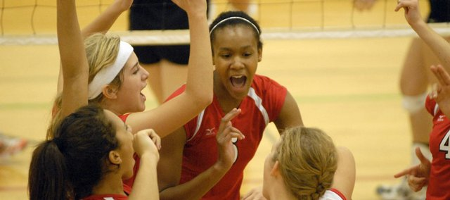 Members of the Lawrence High volleyball team, including Tayler Tolefree, center, celebrate a point against Shawnee Mission Northwest. The Lions went 1-3 and placed seventh at the Joan Wells Invitational on Saturday at LHS.