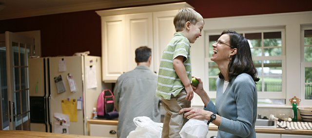 Betsy Six, right, shares a laugh with her youngest son, Will, 3, while her husband, Steve Six, unpacks groceries. Betsy Six is president of the Hillcrest School Parent Teacher Organization and also works for Kansas University's School of Law.