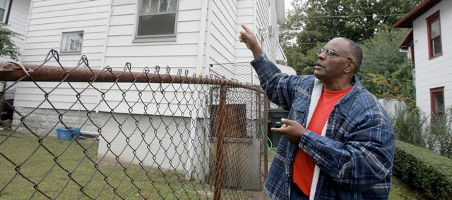Robert Dillon points to the upstairs bedroom in Akron, Ohio, where neighbor Addie Polk, age 90, is believed to have shot herself. Rather than face eviction on foreclosure, Polk apparently shot herself in the chest when deputies came to her neatly kept home on Oct. 1.