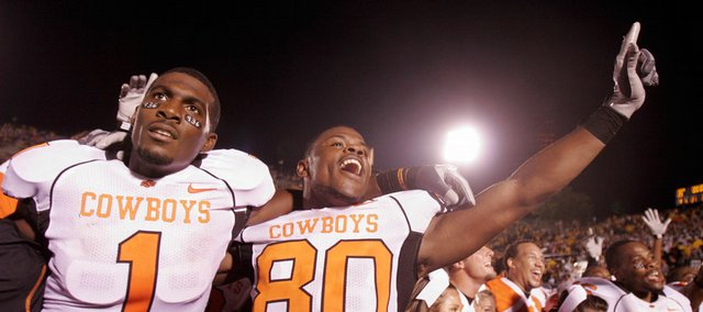 Oklahoma State&#39;s Dez Bryant, left, and DeMarcus Conner celebrate after defeating Missouri, 28-23. The victory Saturday in Columbia, Mo., derailed the Tigers&#39; national-title hopes and propelled OSU to No. 8 in the latest Associated Press poll.