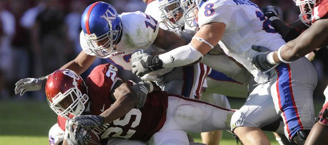 Kansas defenders James Holt, left, Richard Johnson Jr., and Joe Mortensen wrestle down Oklahoma running back Justin Johnson during the third quarter Saturday, Oct. 18, 2008 at Memorial Stadium in Norman, Oklahoma.