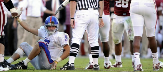 Kansas quarterback Todd Reesing is helped up from the turf after being sacked by the Oklahoma defense. Reesing threw for 342 yards, but was intercepted twice and sacked five times in a 45-31 loss to the Sooners on Saturday in Norman, Okla.