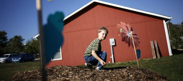 Jacob Lehrman, 7, plays on a mulch pile while his mother, Amber Lehrman, of Lawrence, volunteers at a community garden Sunday at the Faith Church of the Nazarene, 1020 Kasold Drive. The church is building the garden with the help of the Lawrence Sustainability Network and community volunteers. The recent economic crisis has provided extra incentive to reduce, reuse and recycle.