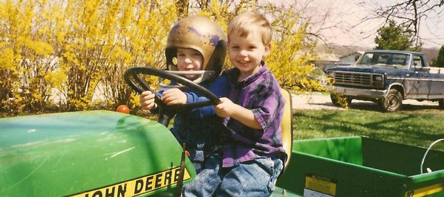 Free State senior Matt Green, left, and Lawrence High senior Jake Green are seen on this John Deere tractor in a photo from their days as youths. Matt and Jake, cousins who have been close since childhood, will appear on opposite sidelines Friday when LHS plays host to FSHS at 7:30 p.m.