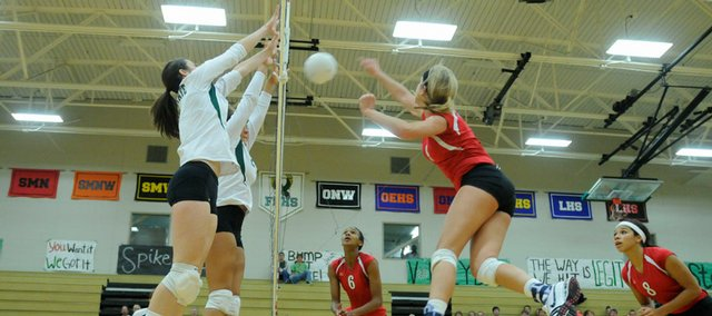 A pair of Free State players, left, team up to block Lawrence High's Mary Coldsnow. The Firebirds beat the Lions, 3-0, Thursday at FSHS.