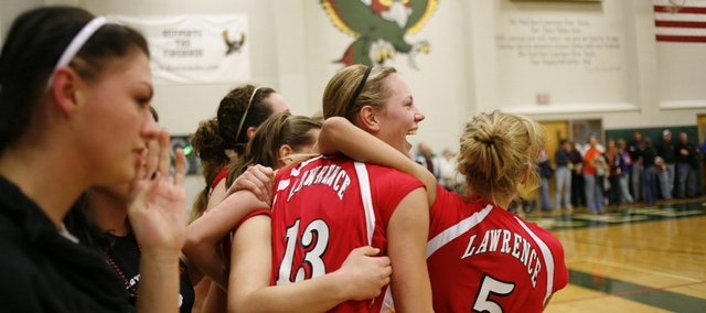 Lillian Schoenwise (13) and others from Lawrence High School jump off the bench in celebration as the Lions defeat Free State High School in the first round of sub-state play Saturday, Oct. 25, 2008 at FSHS.