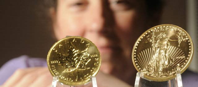 Joleen Neher, co-owner of Kansas Coin Connection, says there's been a local and national run on gold coins causing prices to skyrocket. At left is a Canadian Maple Leaf gold coin and at right is an American Eagle.
