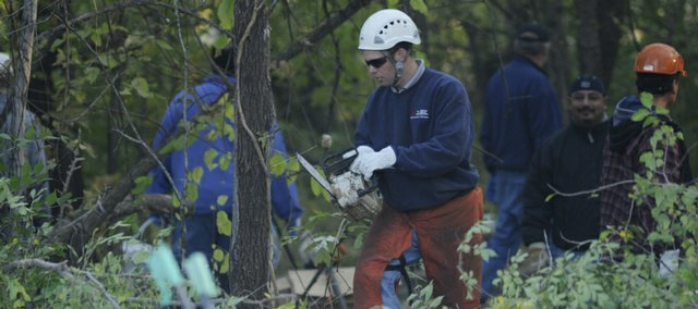 Lawrence city employees clear out a wooded area just north of the Amtrak station, east of the Riverfront Mall, a well-known campsite for local homeless people. Two bodies were found last Friday in the wooded area just north of the Amtrak station, east of the Riverfront Mall. A third homeless person was found dead Wednesday beneath the Kansas River bridge.