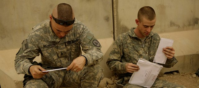 U.S. Army Cpl. Sean Morton, 25, from Boston, left, and a comrade assigned to Killer Troop, 3rd Squadron, 3rd Armored Cavalry Regiment, cast their votes for president Oct. 22 at Forward Operating Base Marez in Mosul, Iraq.