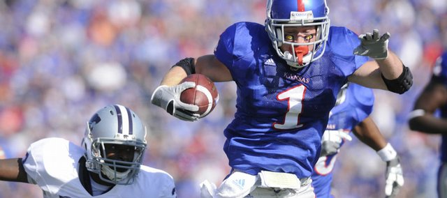 KU running back Jake Sharp evades a Kansas State defender. Sharp had three touchdowns in the first half.