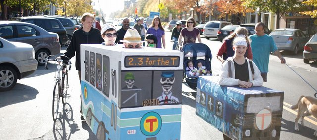 From left in the cardboard buses, Bonnie Cherry, Dave Loewenstein and Clarate Heckler, 12, all of Lawrence, show their appreciation for the Lawrence Transit System, or The T, Saturday, Nov. 1, 2008 during a demonstration and march on Mass. St. The march was held to raise awareness about how The T's future depends on an upcoming vote.