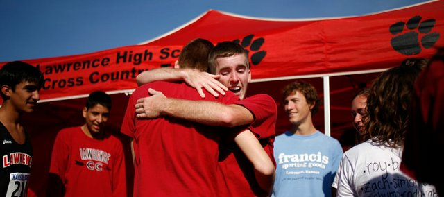 Lawrence High's Ben Wilson celebrates with teammates after learning the Lions had won the Class 6A state cross country title Saturday at Rim Rock Farm.