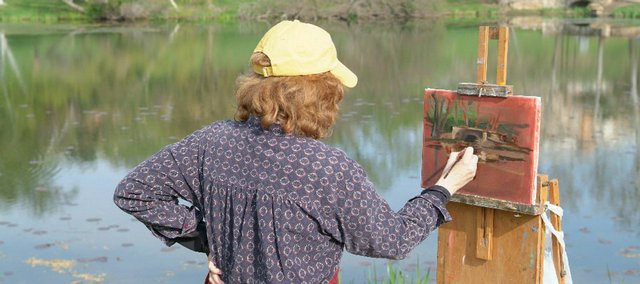 "Mary Binford Miller, of El Dorado, paints a scene at Kansas University's Potter Lake. Miller is one of 63 artists exhibiting in ""A Spring Day on the Hill"" at SouthWind Gallery in Topeka."