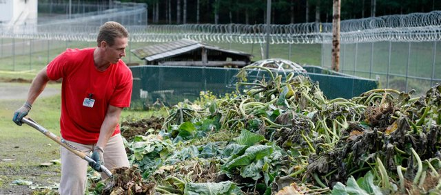 Inmate Robert Knowles pitches plant stalks into a compost pile Oct. 17 at the Cedar Creek Corrections Center in rural southwest Washington. The minimum-security prison has adopted many environmental and cost-saving practices.