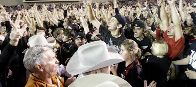 Texas Rangers escort Texas football coach Mack Brown, bottom left, through a throng of Texas Tech students on the field after the Red Raiders upset the No. 1 Longhorns, 39-33, in dramatic fashion on Saturday in Lubbock, Texas.
