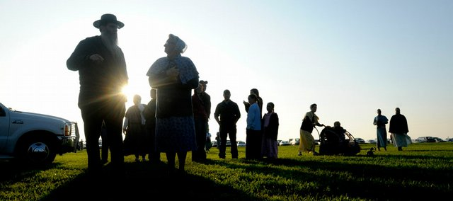 A steady stream of Old German Baptist Brethren makes their way to a tent-raising at the church conference south of Lawrence in this May 2008 file photo. This image demonstrates both a silhouette and a hint of lens flare.